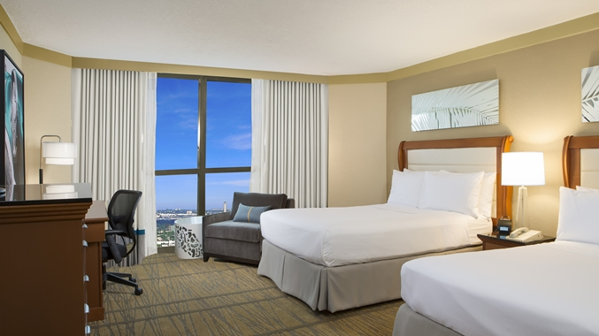 A hotel room featuring 2 freshly made beds and a view of the blue sky over Miami.